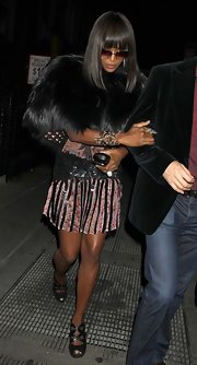 Naomi Campbell offset her flirty striped frock with an over-the-top fur capelet.