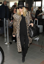 Nicole donned a faux leopard fur coat with her black ensemble at the airport.