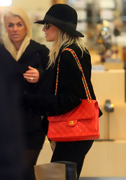 Nicole Richie gave her monochromatic look a festive pop with a classic red Chanel jumbo flap bag.