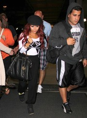Nicole Polizzi departed LAX carrying a stylish black leather tote by Michael Kors.