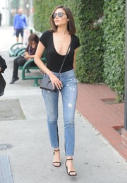 Olivia Culpo took a stroll in West Hollywood wearing a dangerously low-cut black tee by Are You Am I.