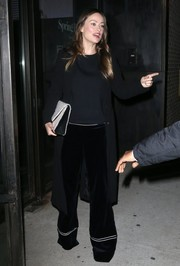 Olivia Wilde enjoyed a night out in New York City wearing a black wool coat over a matching shirt and velvet wide-leg pants.