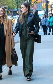 Olivia Wilde went shopping in NYC looking stylish in a forest-green jumpsuit teamed with a black leather jacket.