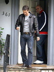 Olivier dons a classic black leather jacket with a brown leather belt.