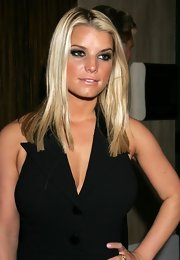 A smokey eyed Ms. Simpson shows off a stick straight center-parted cut. This modern blunt cut look is simple and polished.