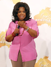 Oprah Winfrey wore a simple pink button-down and tan slacks at the 'Ultimate Australian Adventure' press conference.