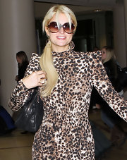Paris Hilton grinned in a pair of oversized round tortoiseshell sunglasses.