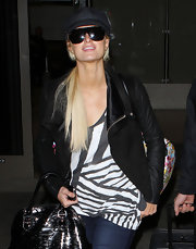 Paris Hilton returned from Brazil in black oversize shield sunglasses.