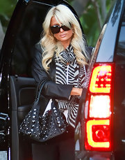 Paris Hilton worked the tough chic look with a studded leather purse. The embellished bag matched a leather jacket and on-trend zebra print scarf.