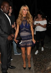Paris Hilton donned a mixed-pattern lace mini dress for a party in West Hollywood.