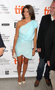 A small neutral clutch keeps the focus on Penelope Cruz's dress and glowing skin.