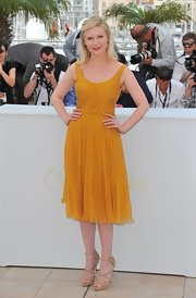 Kirsten Dunst balanced her feminine mustard frock with seriously sexy nude suede Ontario sandals.