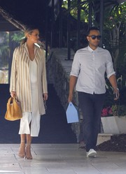 Chrissy Teigen looked impeccable in a gold and white striped coat by The Row layered over a midi dress while out on a lunch date.