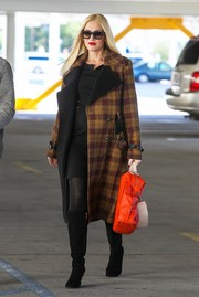 Gwen Stefani made sure she was completely warm and stylish by teaming knee-high black suede boots with her coat.