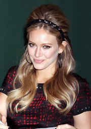 Hilary Duff rocked a 1960s inspired 'do at the signing of her book 'Devoted'. Her half up, half down style was accented with a spiky black headband.