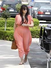 Kim Kardashian looked bright and cheerful in a peach-colored maternity dress while out with her family after church.