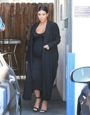 Kim Kardashian visited a Los Angeles studio wearing an all-black coat, pencil skirt, and sheer top ensemble.