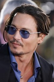 Johnny Depp is wearing silver framed aviator glasses with blue glass.