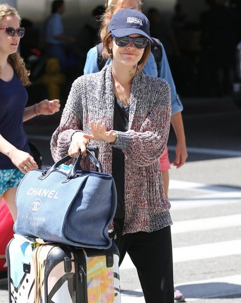 Rachel Bilson caught a flight to LAX carrying a full-packed Chanel tote along with a colorful rollerboard.