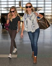 Reese kept her travel look simple and chic with a pair of skinny blue jeans.