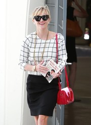 Reese Witherspoon's red leather shoulder bag went flawlessly with her black-and-white outfit.