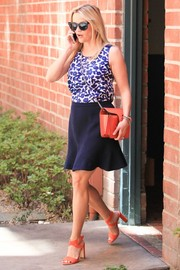 Reese Witherspoon opted for orange accessories, including a pair of stylish cross-strap sandals.