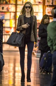 Rosie Huntington-Whiteley finished off her stylish airport ensemble with black suede mid-calf boots by Balmain.
