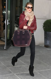 Rosie bundled up in a chic burgundy jacket and black ankle boots.