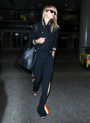 Rosie Huntington-Whiteley arrived on a flight at LAX looking sporty-chic in a black Saint Laurent varsity jacket.