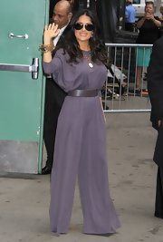 Salma stunned in a wide-legged, draped jumpsuit in a rich grape hue.