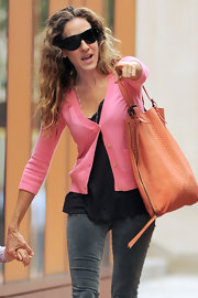 SJP was out and about NYC with daughter Marion in a pink cardigan paired with an orange python-printed tote.