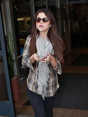 Selena bundled up in this cute and casual plaid button-up and scarf.