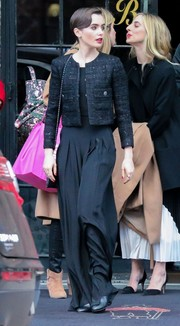 Lily Collins paired her jacket with fluttery black pants.