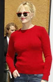 The actress paired her scarlet cable-knit sweater with a pair of matching, playful wayfarer shades.