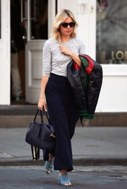 Sienna Miller paired her top with navy wide-leg pants.