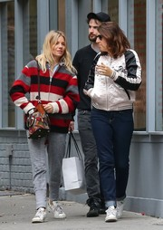 Sienna Miller accessorized her look with a printed shoulder bag by Maison Margiela.