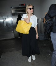 Sienna Miller brightened up her airport outfit with a yellow shopper bag by Roger Vivier.