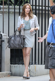 Katie Cassidy paired her suit skirt with a grey leather tote.