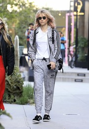 Suki Waterhouse dressed down in a gray Adidas track jacket for a lunch out.