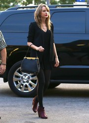 Taylor Swift injected subtle color into her look with a pair of maroon ankle boots.