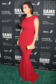 Kim Kardashian accented her stunning red mermaid gown with a gold Emile clutch embellished with champagne crystals.