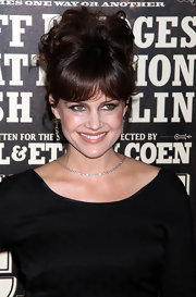 Carla Gugino added some height to her look with a curly updo complete with wispy bangs.