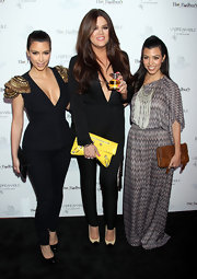 At the launch of her new fragrance, Unbreakable, Khloe showed she's not afraid to be a little silly. The reality maven accessorized her Gucci jumpsuit and Balenciaga clutch with her very own Kardashian Glam SillyBandz!