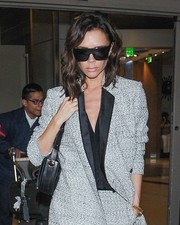 Victoria Beckham kept her eyes hidden behind a pair of shield sunglasses from her own line while making her way through LAX.