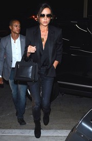 Victoria Beckham completed her airport ensemble with black suede ankle boots by Alaia.
