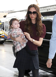 Victoria Beckham teamed her school girl skirt with a maroon princess sleeve sweater over a black collared top.
