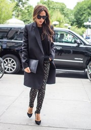 Victoria Beckham topped off her shopping ensemble with a black python clutch, also from her own label.