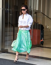Victoria Beckham dressed up her top with a pleated green skirt, also from her label.