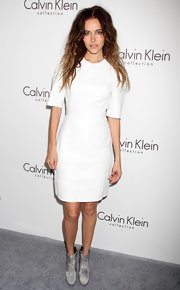 Isabel opted for a pair of worn gray leather ankle boots to complete her pristine white sheath dress.