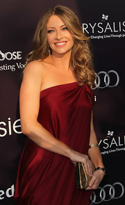 Rebecca Gayheart complemented her draped burgundy dress with a gold and cork hard case clutch.